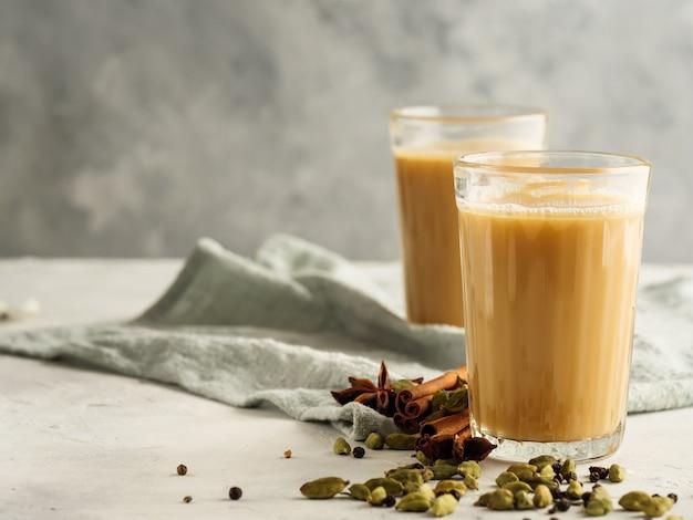 Traditionele indiase drank masala-thee op een lichte achtergrond met kruiden. ruimte kopiëren.