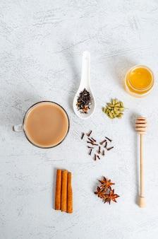 Traditionele indiase drinken masala thee in een glazen beker met ingrediënten voor het koken