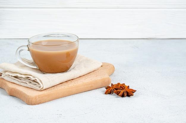 Traditionele indiase drinken masala thee in een glazen beker op een snijplank met een katoenen servet op een lichte ondergrond