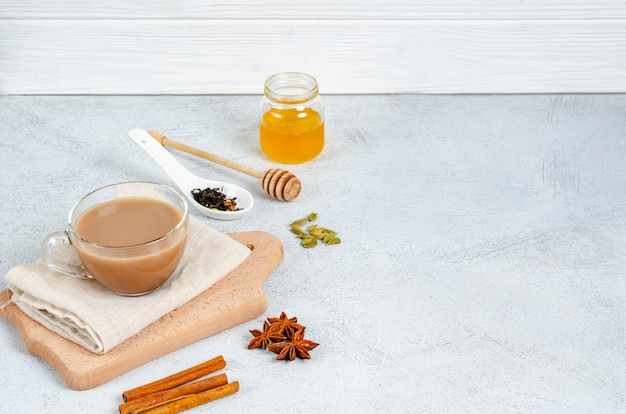 Traditionele indiase drinken masala thee in een glazen beker op een snijplank met ingrediënten voor thee