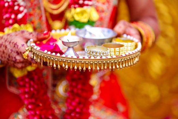 Traditionele indiase huwelijksceremonie in het hindoeïsme puja thali en olielamp in de hand houden