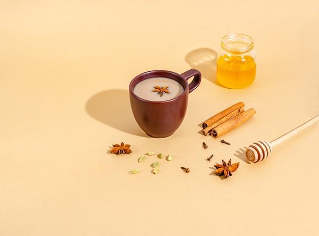 Traditionele indiase thee. masala-thee in een donkere kleikop met ingrediënten