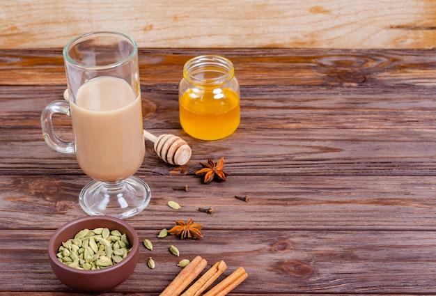 Traditionele indiase thee masala thee in een hoge glazen beker. ingrediënten voor het zetten van thee