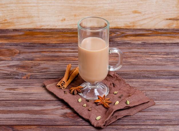 Traditionele indiase thee masala thee in een hoge glazen beker op een donkere servet met kruiden