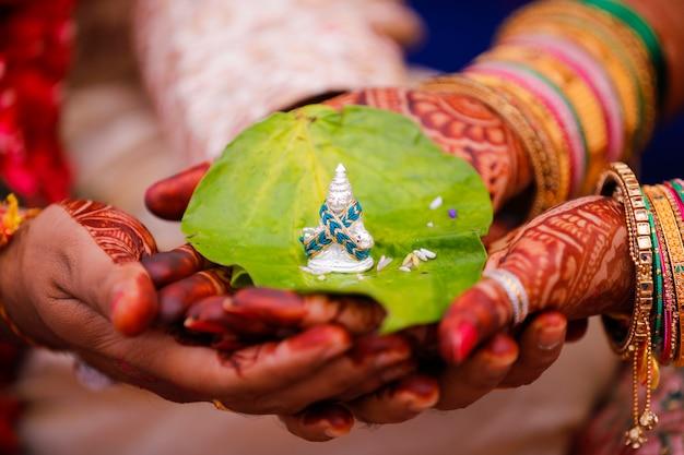 Traditionele indische huwelijksceremonie, de bruidhand van de bruidegomholding
