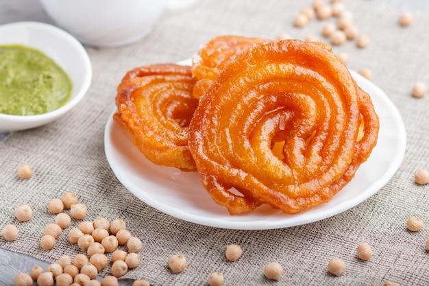 Traditionele indische suikergoedjalebi in witte plaat met muntchutney
