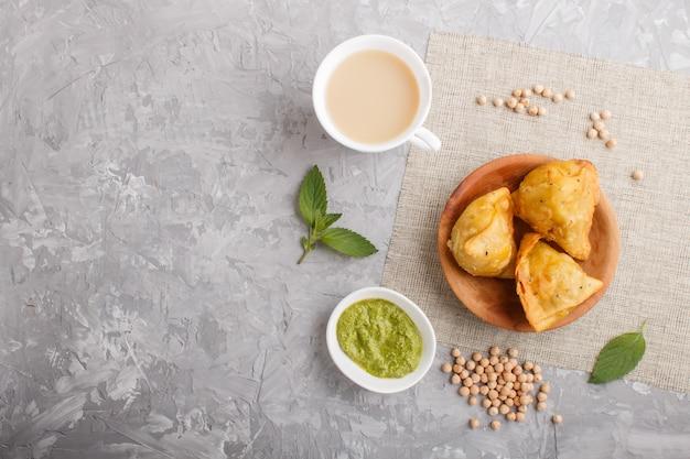 Traditionele indische voedselsamosa in houten plaat met muntchutney op een grijs beton copyspace. bovenaanzicht.