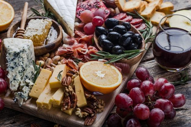 Traditionele italiaanse antipastoplaat. geassorteerde kazen op houten snijplank. brie-kaas, plakjes cheddar, gogonzola, walnotendruiven, olijven, prosciutto, rozemarijn en glas rode wijn. bovenaanzicht