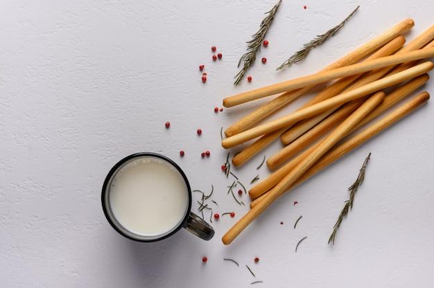 Traditionele italiaanse breadsticks grissini liggen op een licht getextureerde tafel. in de buurt van een mok melk en takjes rozemarijn. bovenaanzicht. ruimte kopiëren