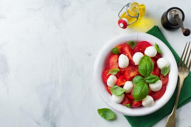 Traditionele italiaanse caprese salade met tomaten, maozzarella kaas en basilicum op een licht marmeren oppervlak in een witte oude keramische plaat