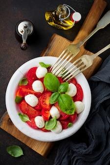 Traditionele italiaanse caprese salade met tomaten, mozarellakaas en basilicum op donkere ondergrond in witte oude keramische plaat