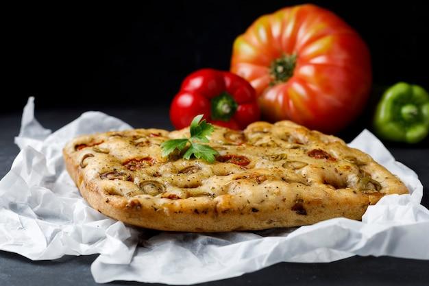 Traditionele italiaanse focaccia met tomaat en olijven