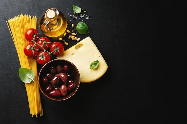 Traditionele italiaanse gerechten achtergrond met spaghetti tomaten kaas olijven en olie op donkere achtergrond.