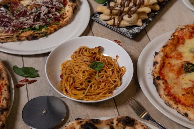 Traditionele italiaanse gerechten. spaghetti, pizza's, typisch napolitaans dessert met nutella. geïsoleerde afbeelding. mediterrane keuken.