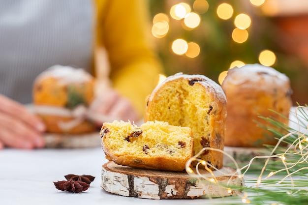 Traditionele italiaanse kerstcake panettone op een rustieke tafel met feestelijke decoraties voor de feestdagen. vrouwelijke handen houden cake vast