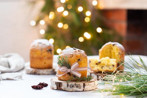 Traditionele italiaanse kerstcake panettone op een rustieke tafel met feestelijke decoraties voor de feestdagen