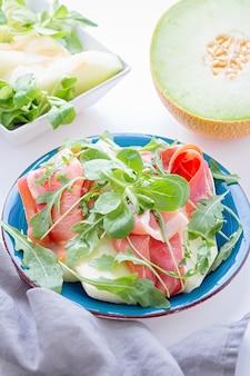 Traditionele italiaanse of spaanse voorgerecht verse meloen met prosciutto of jamon en groene kruiden op blauwe plaat en witte tafel, bovenaanzicht, lichte mediterrane keukenschotel