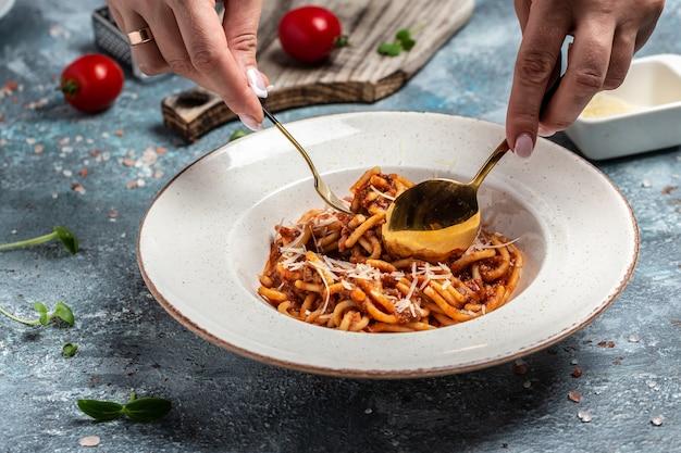 Traditionele italiaanse pasta bolognese met tomaat en vleesgehaktsaus geserveerd in een bord met parmezaanse kaas. voedsel recept achtergrond. detailopname.