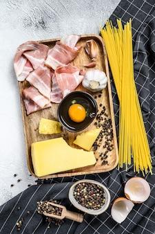 Traditionele italiaanse pasta carbonara-ingrediënten. spek, spaghetti, parmezaanse kaas en pecorino, ei, knoflook