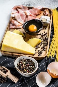 Traditionele italiaanse pasta carbonara-ingrediënten. spek, spaghetti, parmezaanse kaas en pecorino kaas, ei, knoflook. bovenaanzicht