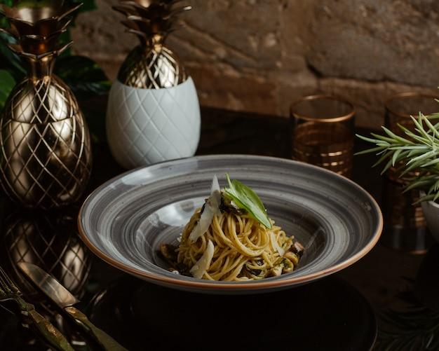 Traditionele italiaanse pasta met champignons, parmezaanse kaas plakjes en oregobladeren in een granieten kom