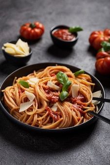 Traditionele italiaanse pasta met tomatensaus, basilicum en kaas op de zwarte, top-down weergave met kopie ruimte
