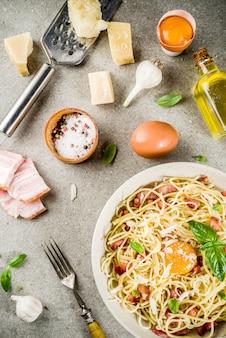 Traditionele italiaanse pasta, spaghetti carbonara met spek, romige saus, parmezaanse kaas, eigeel en verse basilicum