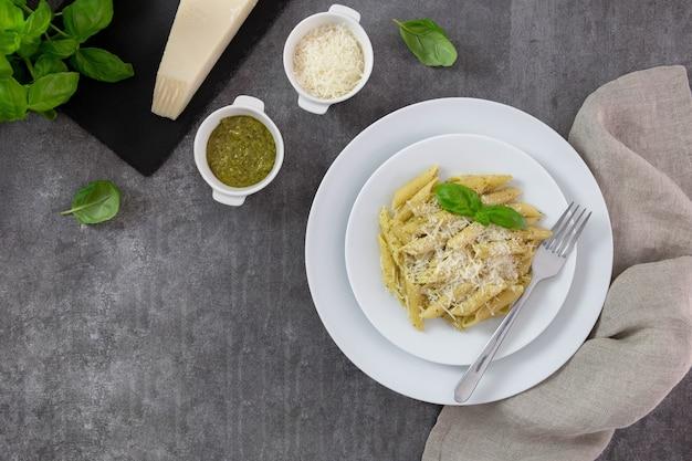 Traditionele italiaanse pennedeegwaren met pesto, basilicum en parmezaanse kaas op witte plaat, donkere achtergrond.