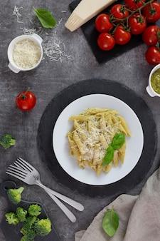 Traditionele italiaanse pennedeegwaren met pesto, basilicum, tomaten en parmezaanse kaas op een witte plaat, op een donkere achtergrond.