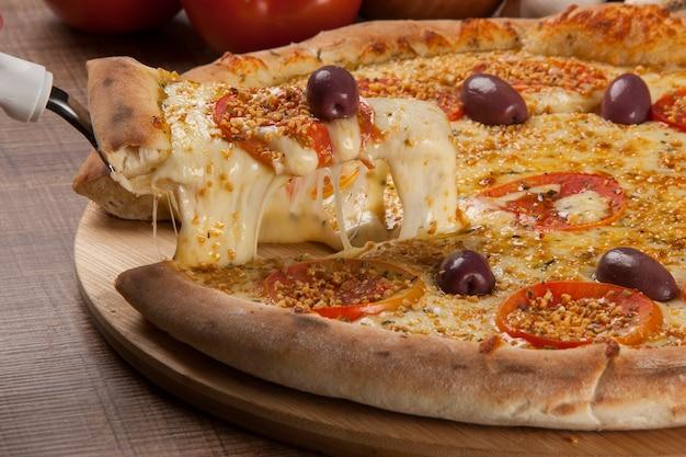 Traditionele italiaanse pizza met ingrediënten op houten.
