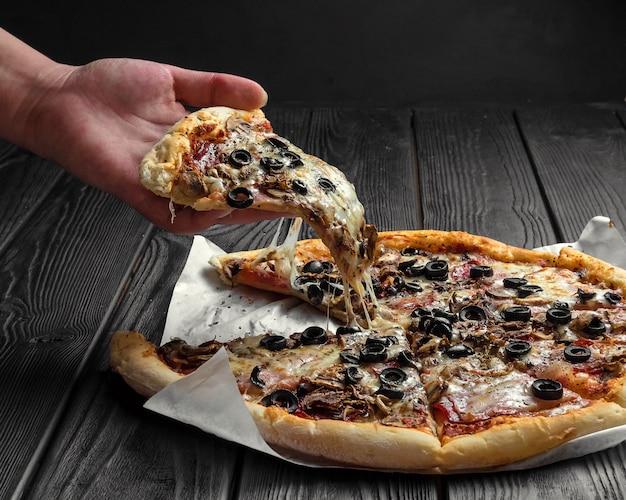 Traditionele italiaanse pizza op donker zwart houten bord, stuk pizza in de hand,