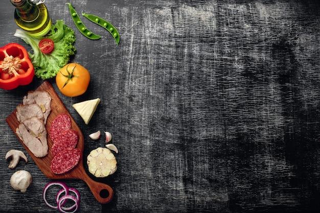 Traditionele italiaanse pizzacalzone met ingrediënten op een steen en een donkere houten gekraste achtergrond
