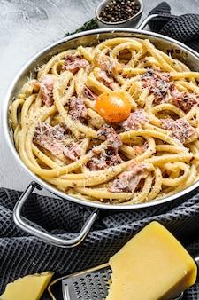 Traditionele italiaanse schotel spaghetti carbonara met spek in een roomsaus in een koekenpan. grijze achtergrond. bovenaanzicht