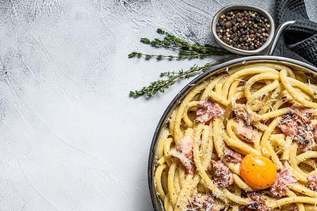 Traditionele italiaanse schotel spaghetti carbonara met spek in een roomsaus in een koekenpan. grijze achtergrond.