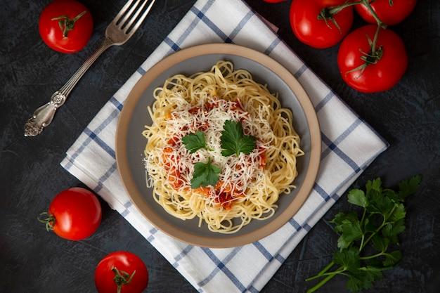 Traditionele italiaanse spaghetti met bolognesesaus met parmezaanse kaas en kruiden, kerstomaatjes, peterselie op een donkere tafel achtergrond, bovenaanzicht.