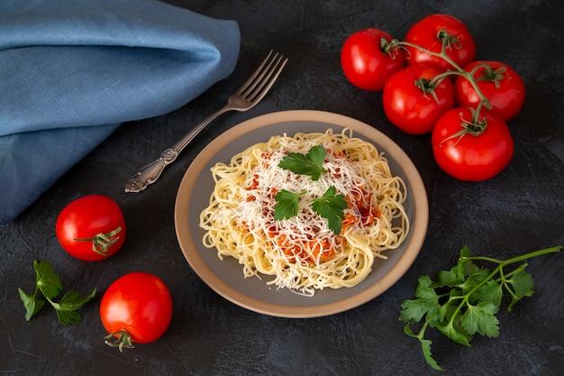 Traditionele italiaanse spaghetti met bolognesesaus met parmezaanse kaas en kruiden, kerstomaatjes, peterselie op een donkere tafel achtergrond.