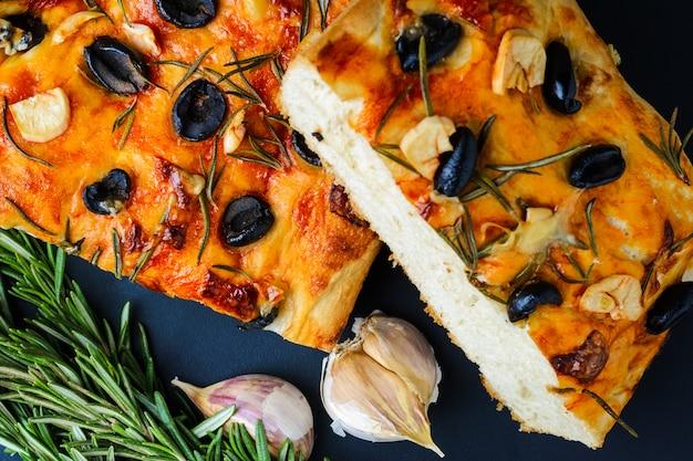 Traditionele italiaanse vegetarische focaccia van zelfgebakken brood met olijven, rozemarijn en knoflook
