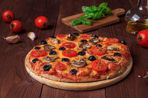 Traditionele italiaanse vegetarische pizza met champignons, cherrytomaatjes, zwarte olijven en basilicum op bruin houten tafel