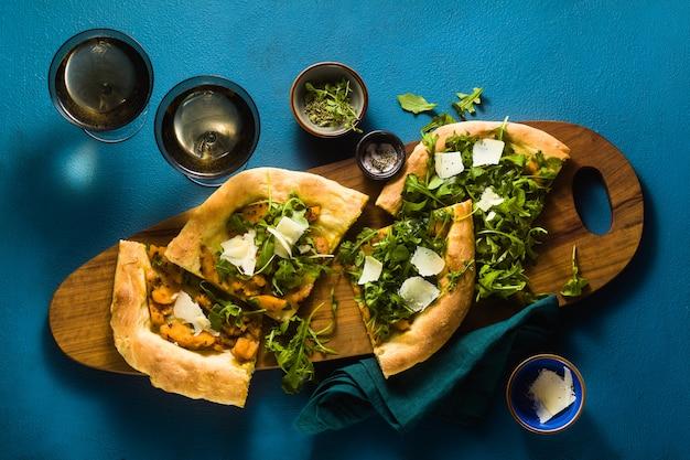 Traditionele italiaanse witte pizza met taleggio en pecorino kaas, gekarameliseerde pompoen en rucola op de blauwe tafel