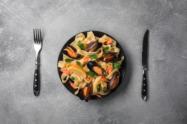 Traditionele italiaanse zeevruchten pasta met mosselen spaghetti alle vongole op stenen achtergrond met garnalen en mosselen