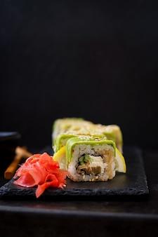 Traditionele japanse gerechten - sushi, broodjes en saus op een zwarte tafel.