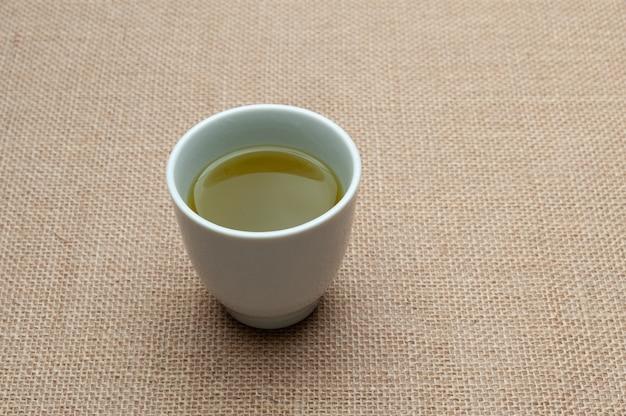 Traditionele japanse groene thee geïsoleerd op jute