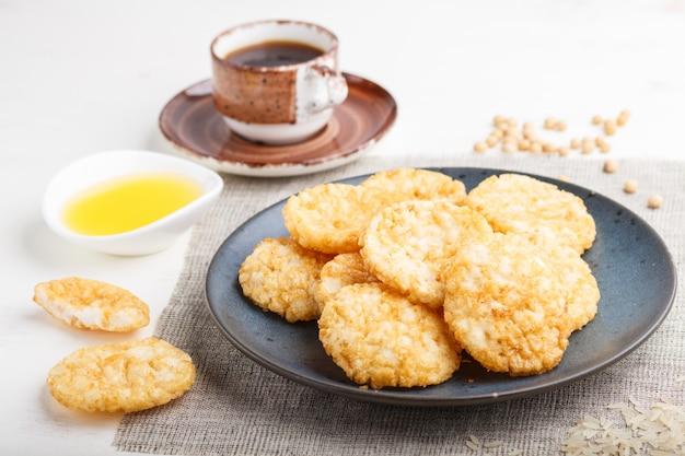 Traditionele japanse rijst chips koekjes met honing en sojasaus op een blauwe keramische plaat en een kopje koffie