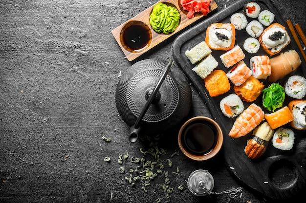 Traditionele japanse sushi en broodjes met groene thee in de theepot.