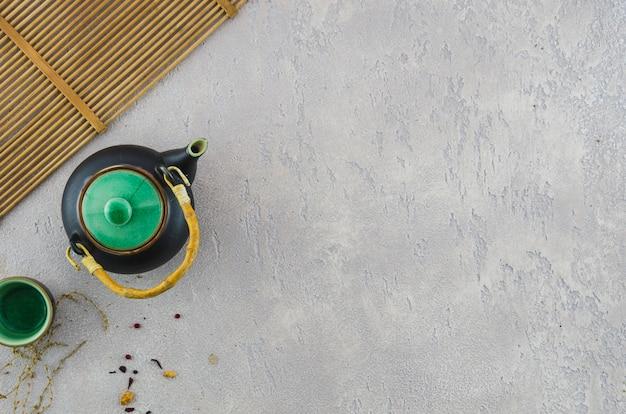 Traditionele japanse theepot en kop dichtbij placemat op grijze achtergrond