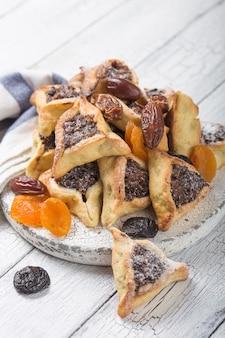 Traditionele joodse hamantaschen-koekjes met gedroogde abrikozen, dadels. purim viering concept. ð¡arnival vakantie achtergrond. selectieve aandacht. kopieer ruimte.