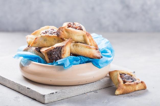 Traditionele joodse hamantaschen-koekjes met gedroogde abrikozen, dadels. purim viering concept.