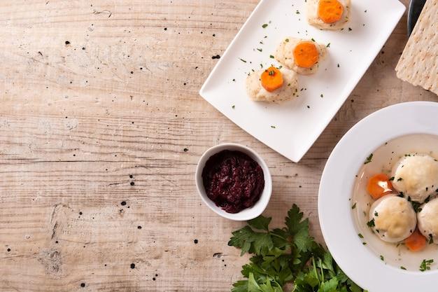 Traditionele joodse matzah balsoep, gefilte vis en matzah brood op houten tafel
