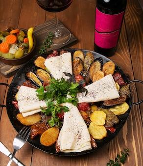 Traditionele kaukasische zakje ici met gebakken kip, aubergine, aardappelen, tomaten, courgette en geserveerd met lavash, peterselie, turshu.