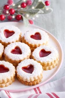 Traditionele kerst linzer koekjes gevuld met aardbeienjam op lichte tafel met xmas decoraties